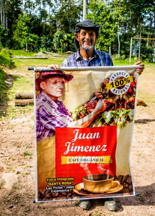 Cenfrocafe member farmer Juan Jimenez holding up a poster for his organic fair trade coffee.